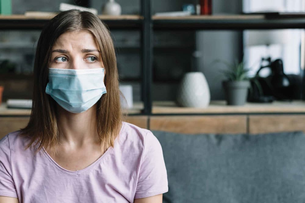 worried woman wearing mask in office